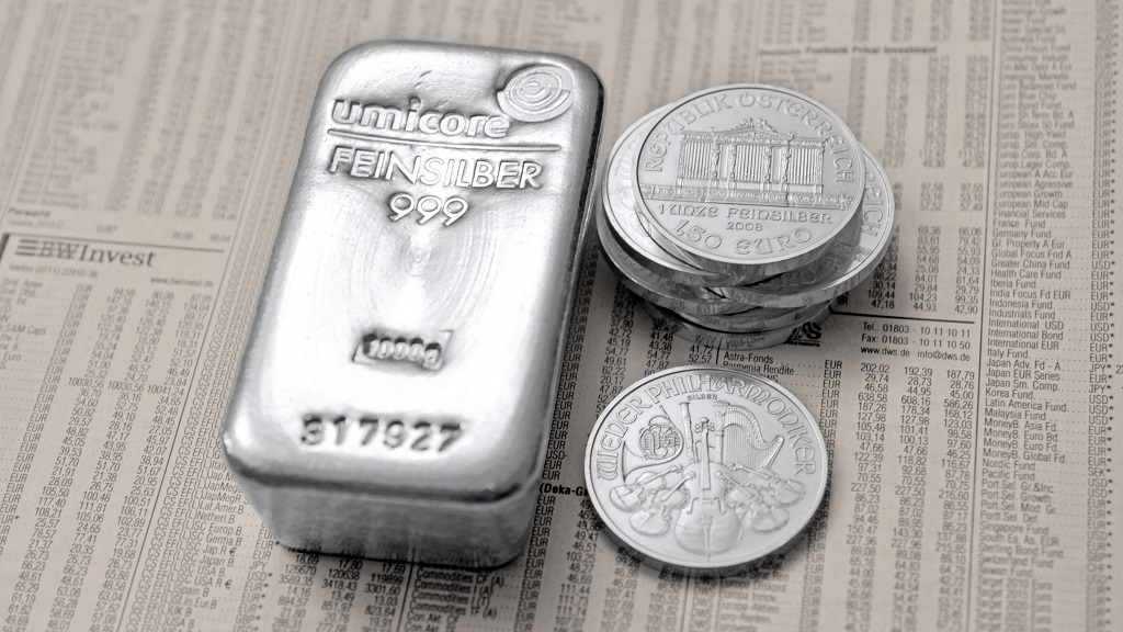 A 1-kilo silver bar and a Vienna Philharmonic coin appearing on the economic section of a newspaper